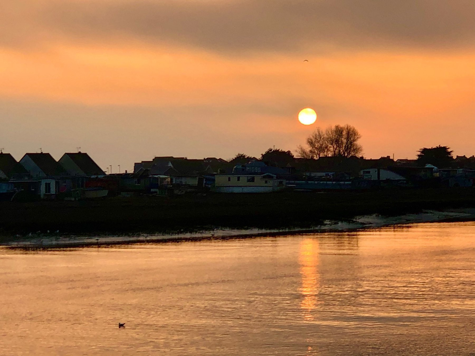 the sun sets over the Shoreham-by-Sea houseboats.