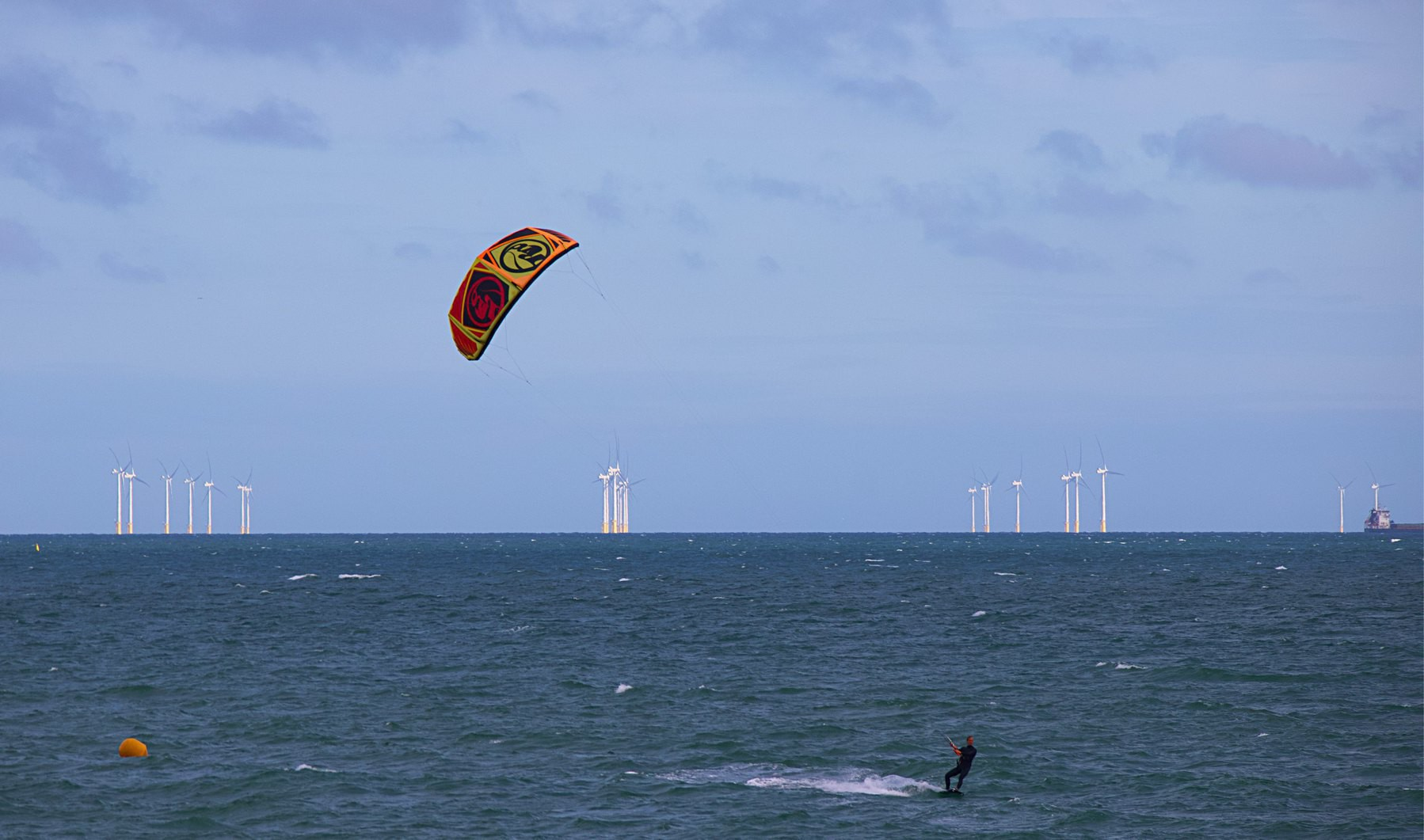 A kitesurfer surfing in front of the Rampion Wind Farm.