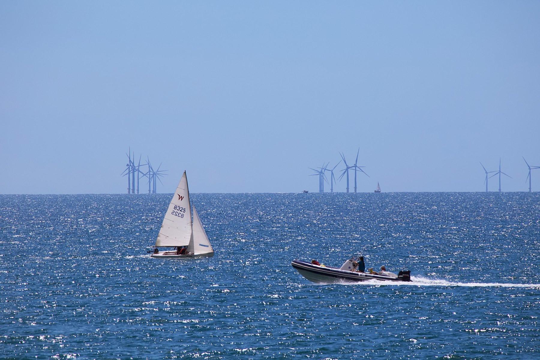 Various boats off Shoreham Beach, with Rampion wind farm on the horizon.
