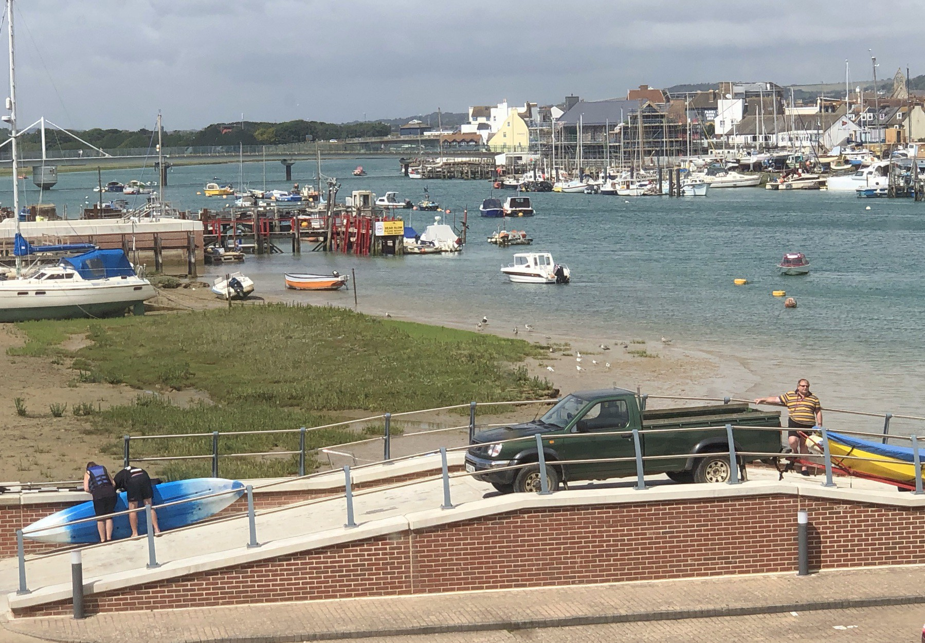 Boaters and SUPers waiting to launch from a slipway.