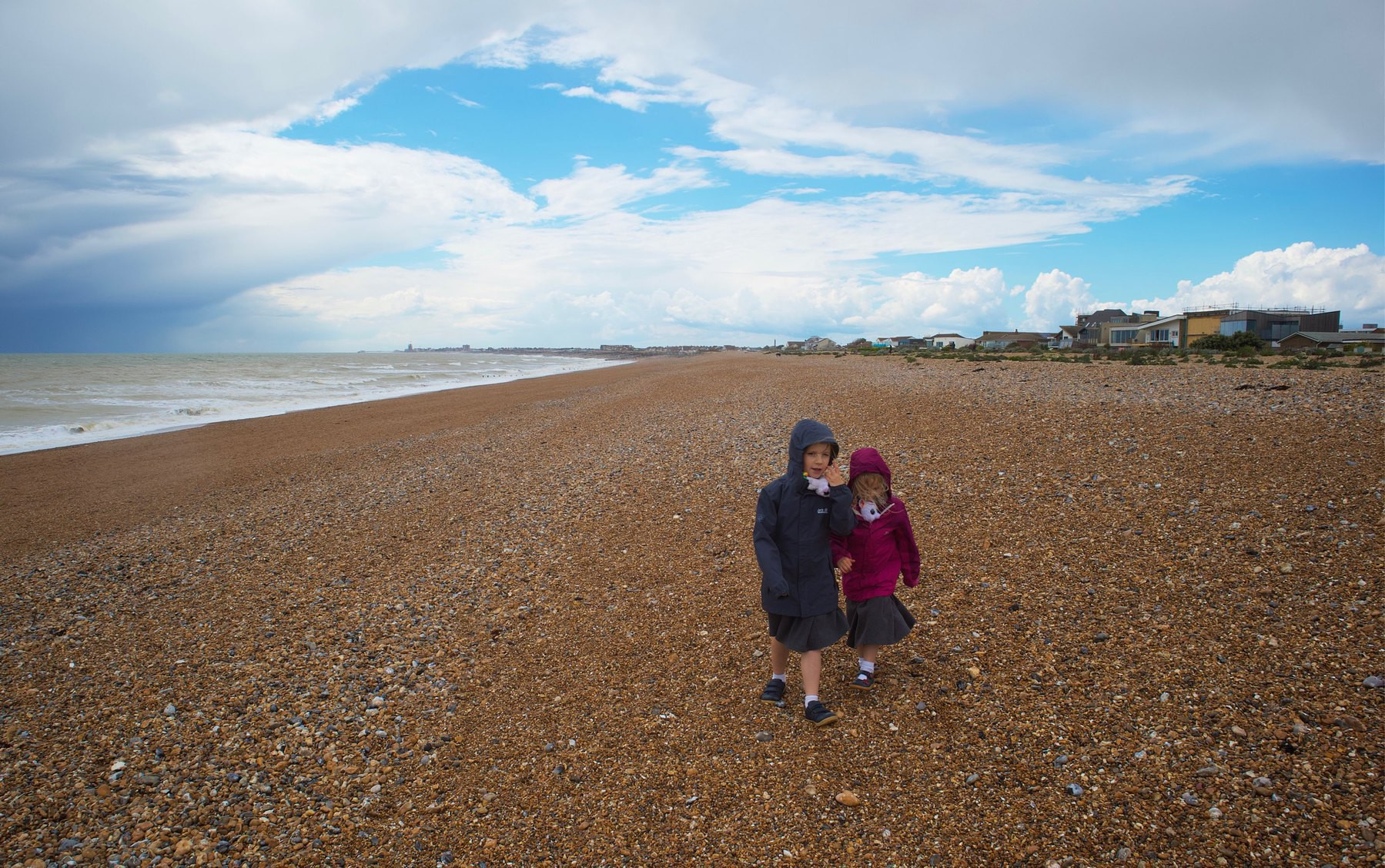 Two girls ealking on a blustery Shoreham Beach.