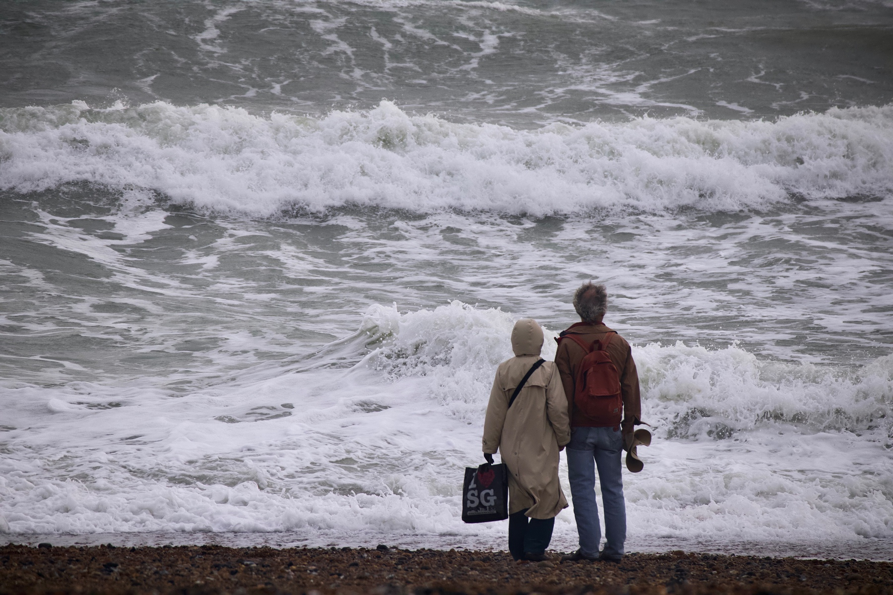 A couple stands on Shoreham Beach facing the waves.
