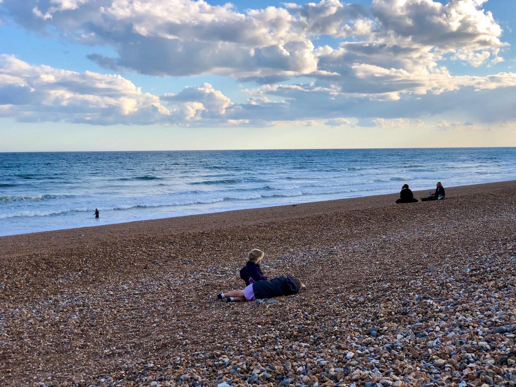 A few people enjoying Shoreham Beach in the evening.