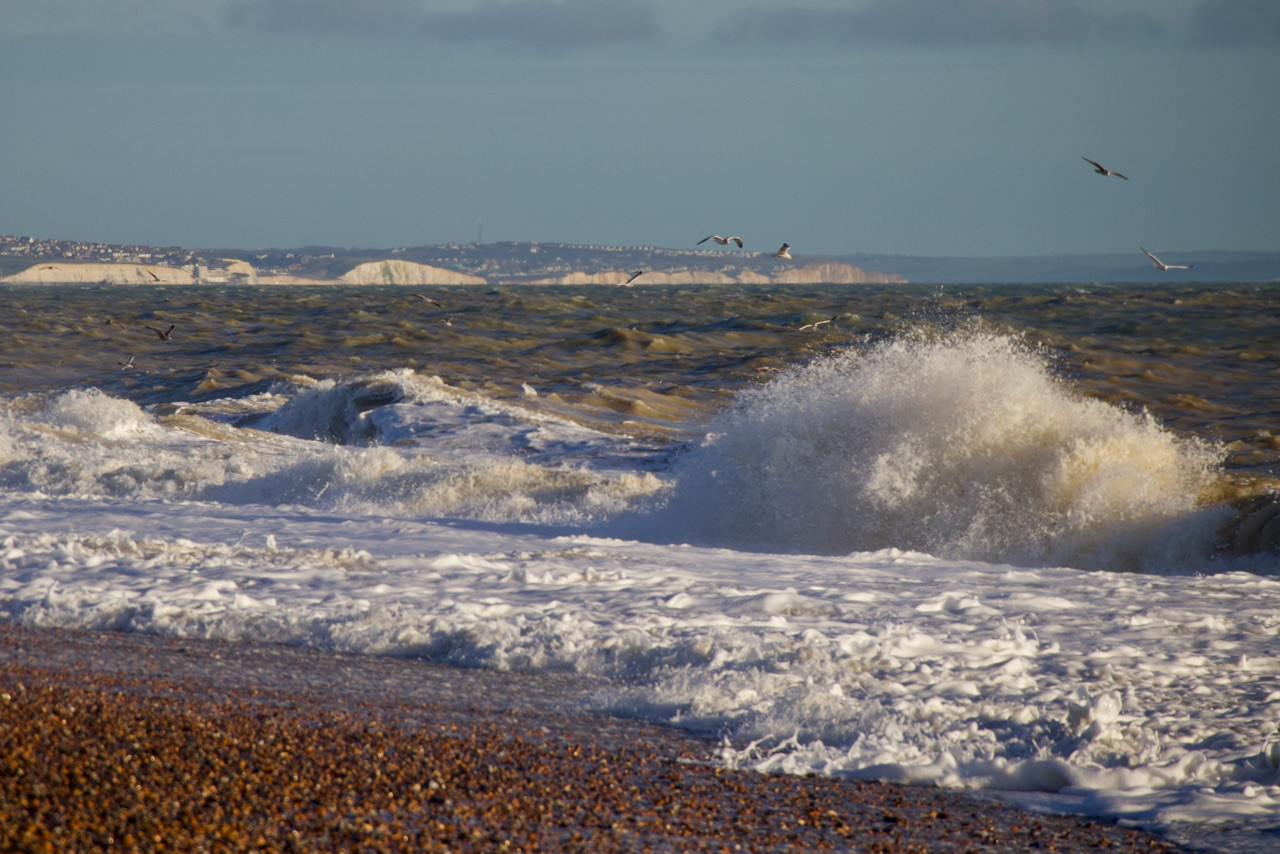 Waves on Shoreham Beach with the white cliffs of Sussex in the background /></p>    </section>       <script type=