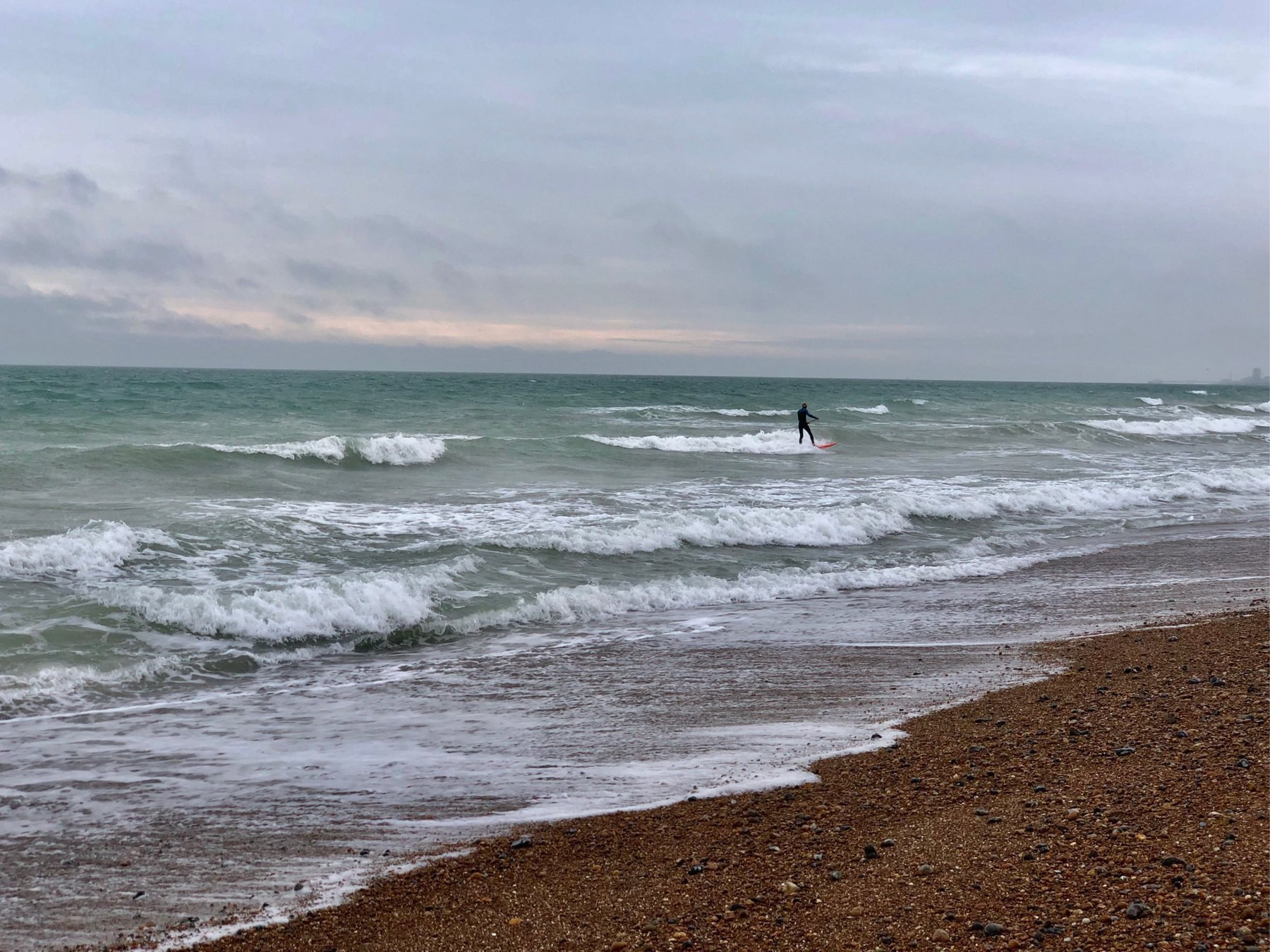 A surfer in the sea off Shoreham Beach.