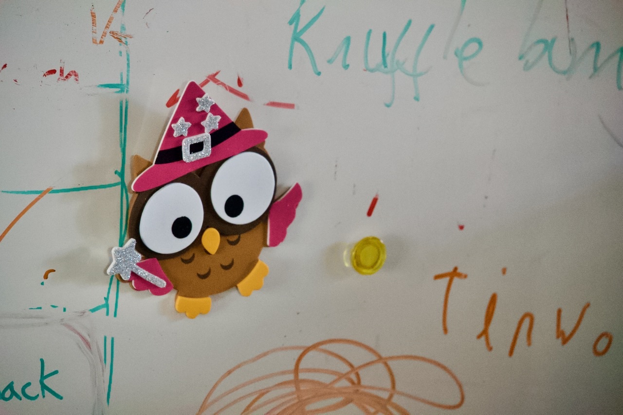 A whiteboard with childrens' scribblings and a crafted owl.