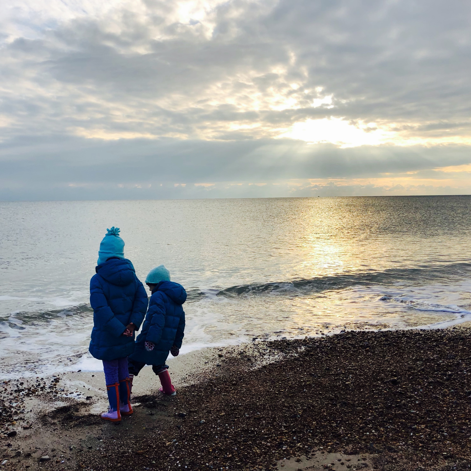 Two girls on a winter shoreline