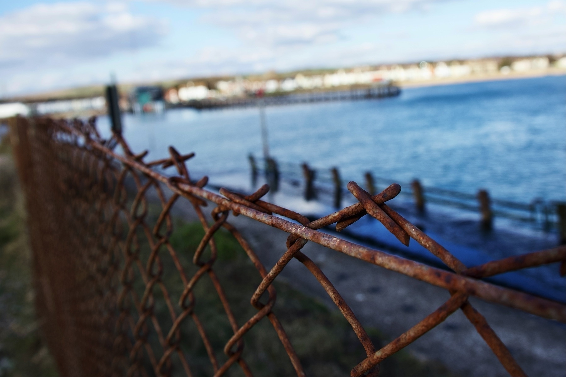 A barbed wire fence blocking access to the water's edge on Shoreham Beach.