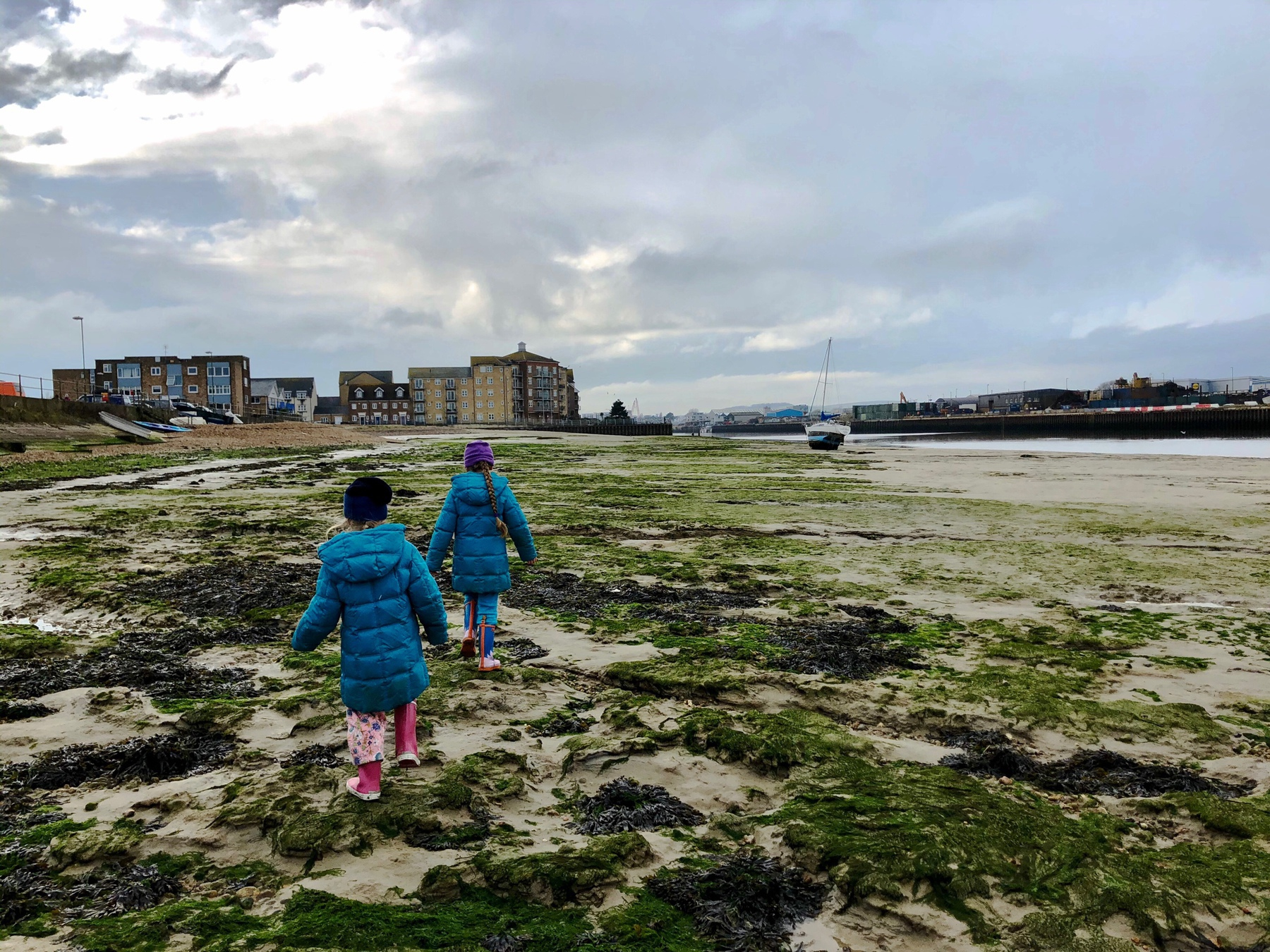 Two girls walking in the Adur at low tide.