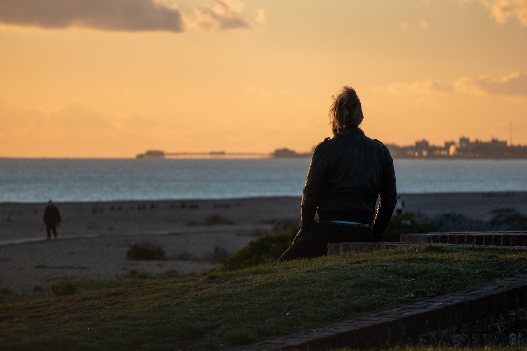A man sits on the edge of Shoreham Fort, watching the sun set over Worthing.