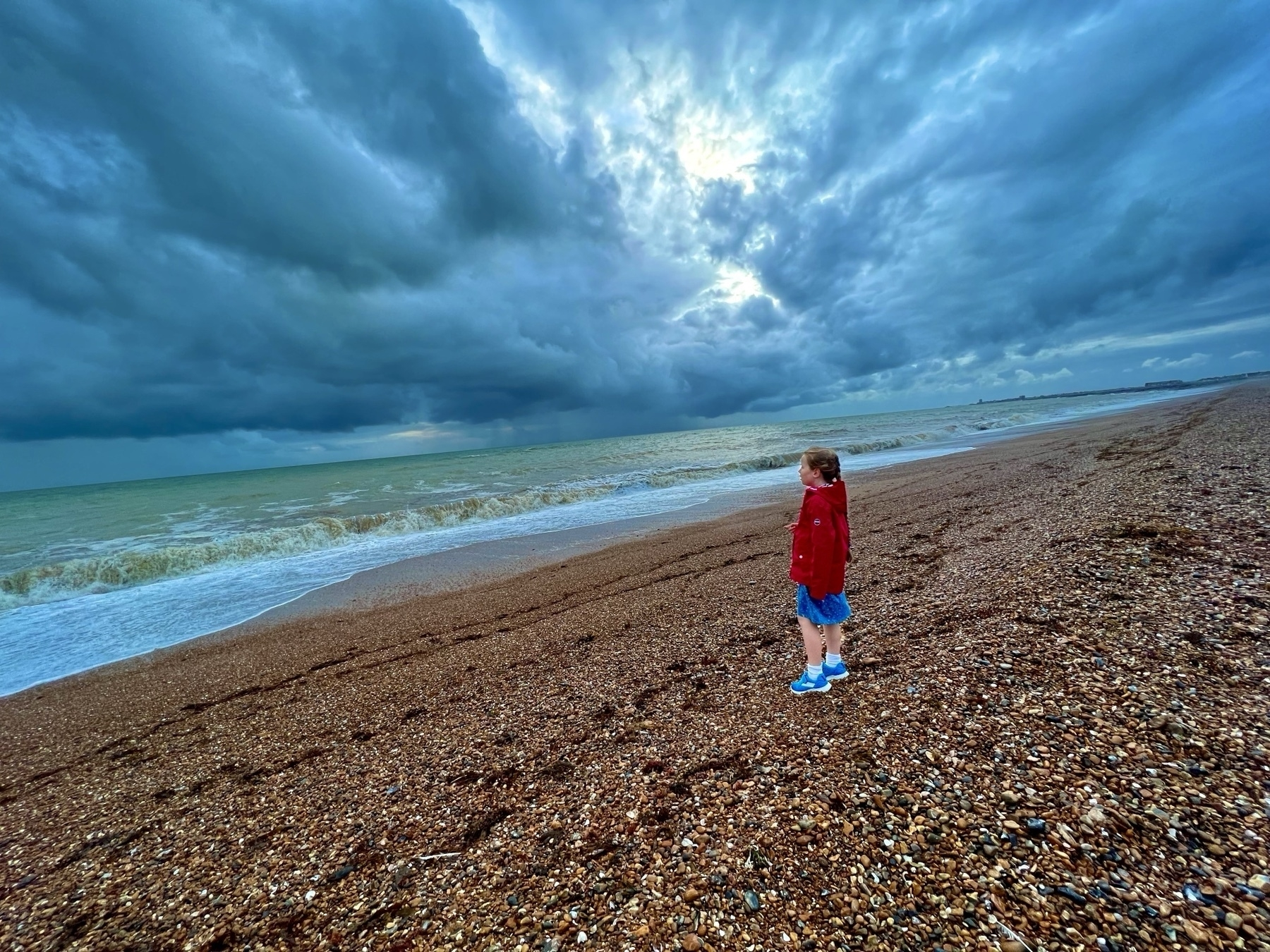 A girl standing on a shingle beach with stormy clouds overhead.