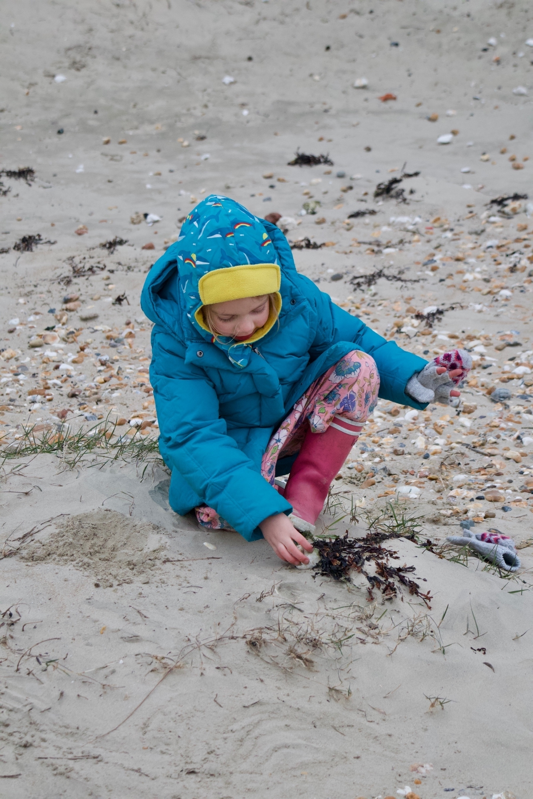 A girl, wrapped up for winter weather, playing on a beach.