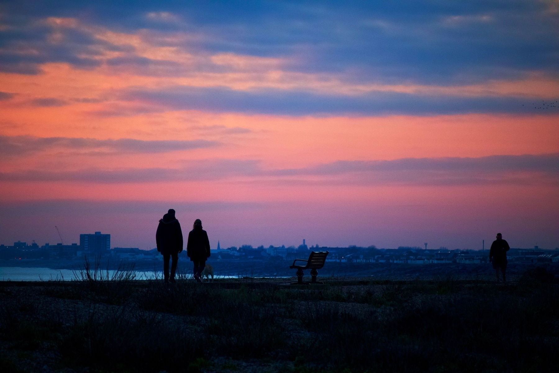 Dusk over Shoreham Beach, looking towards Worthing, with walkers in the foreground