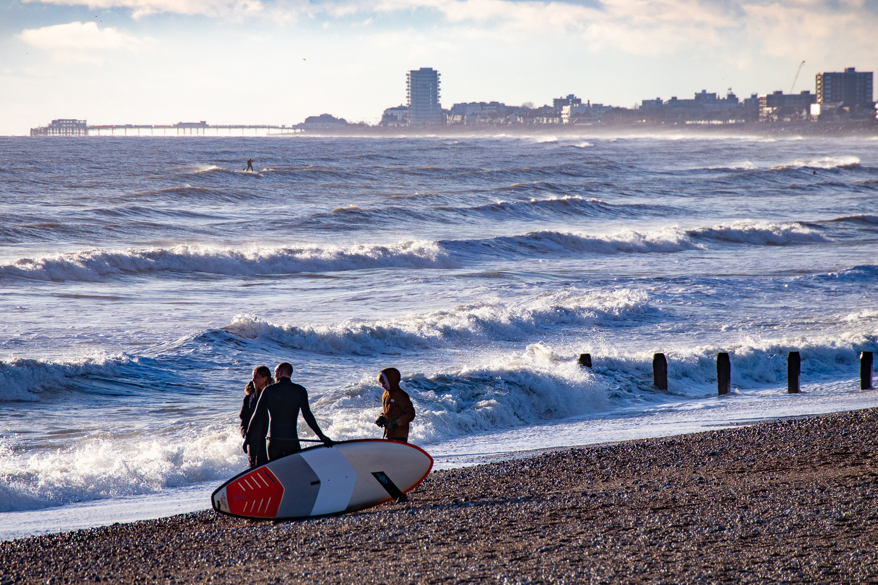 Surfers enjoying Shoreham Beach, with a view of Worthing Pier.