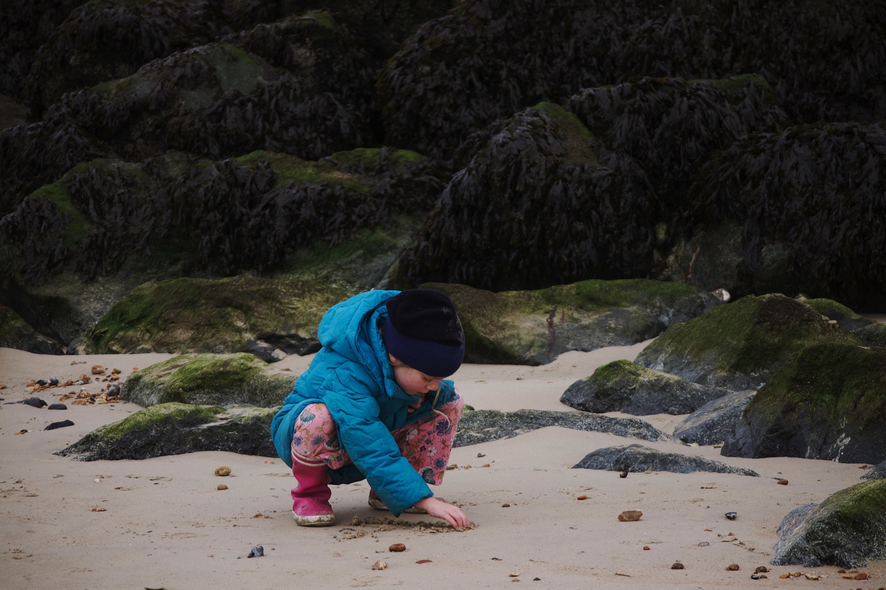 A girl digging in the sand by a pile of rocks at low tide.
